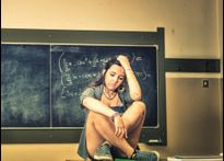 Girl sitting on school desk (iStock)