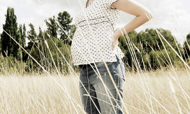 Pregnant woman standing in field (iStock)