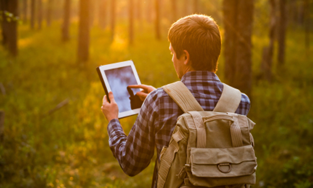 hiker with computer tablet (iStock)