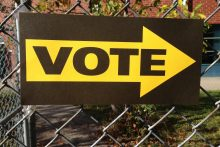 Vote sign hanging on a fence