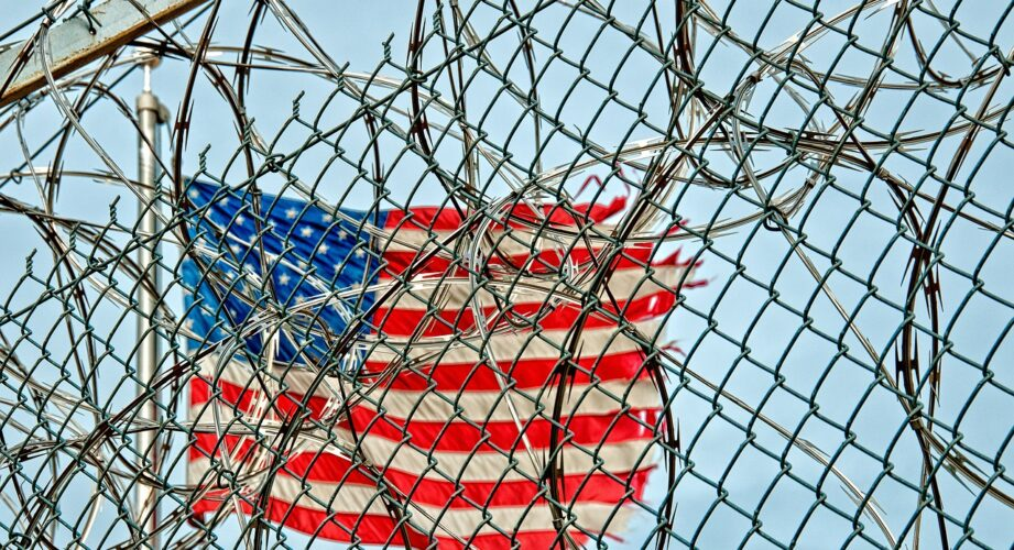 American flag behind a prison fence