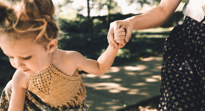 Woman holding the hand of a child.