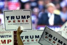 Donald Trump supporters holding signs at a campaign rally