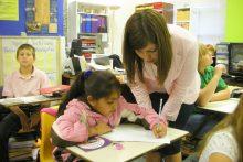 Teacher helping student in classroom
