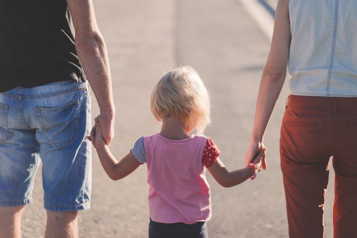 Young child standing with parents