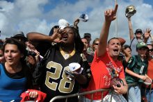 Football fans yell for their favorite players .