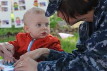 Woman wearing military uniform interacting with toddler