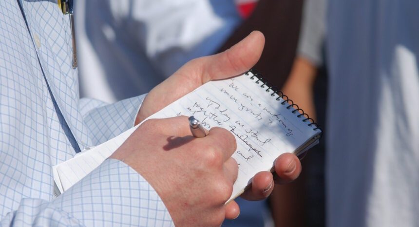 reporter writing in notebook