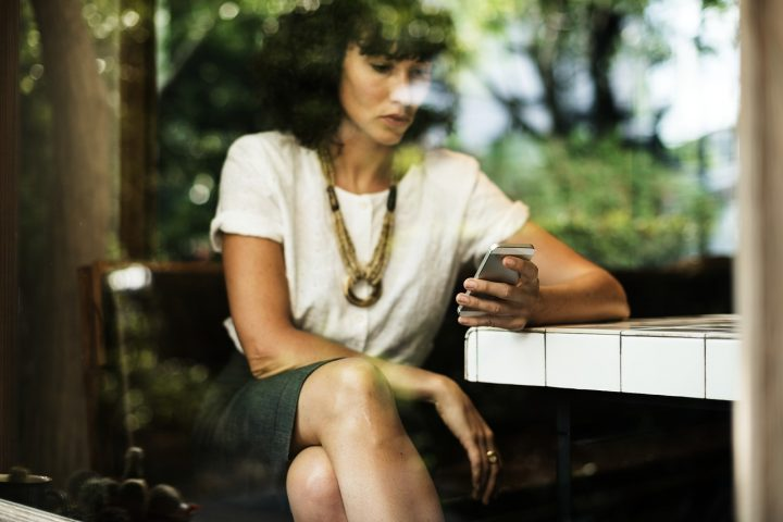 woman looks at phone