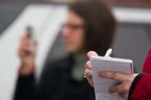 Person writing in reporter's notebook