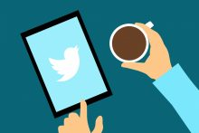 Illustration of person holding tablet showing Twitter symbol