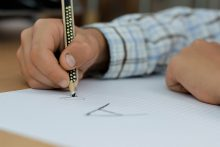 """Child writing the letter """"a"""" on paper with a pencil"""