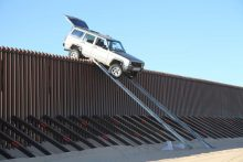 Vehicle stuck on top of a border barrier.
