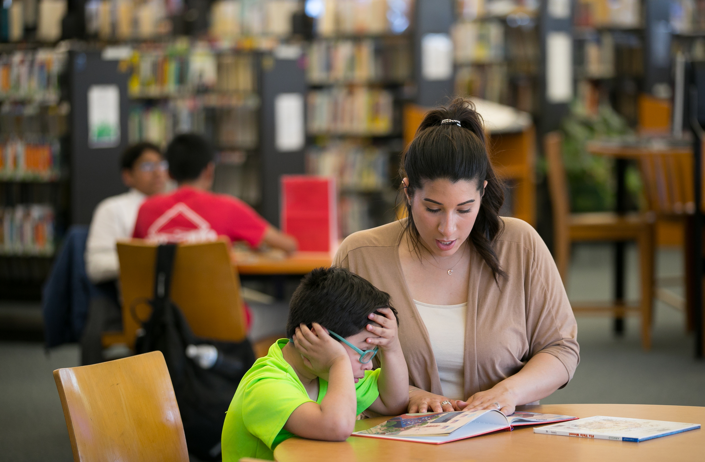 Cristine Gonzalez, right, does reading homework with her six-year-old son Dean Pagan, left, at their local library branch, Northeast Philadelphia, Wednesday, May 2, 2018. Dean was severely lead poisoned at Comly Elementary School. JESSICA GRIFFIN / Staff Photographer