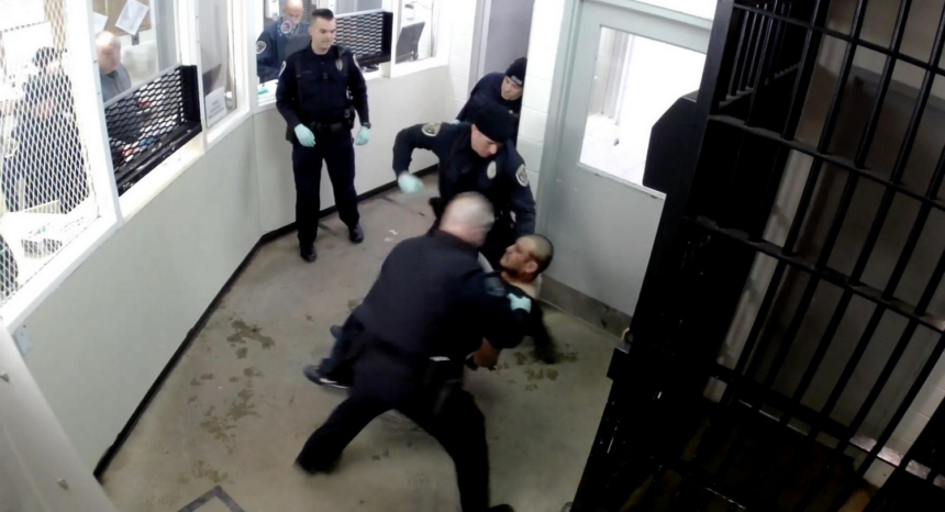 Screenshot of video showing police hitting handcuffed man