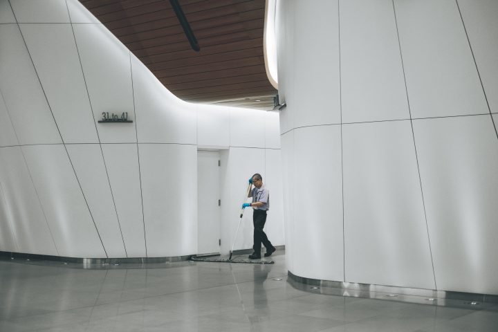 A janitor sweeps in the lobby of a large office building