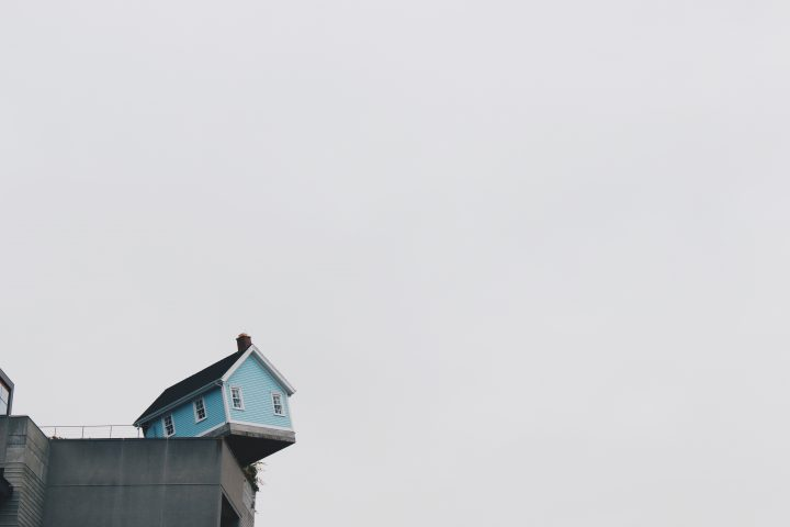 Image of a blue house on the edge of a concrete structure.