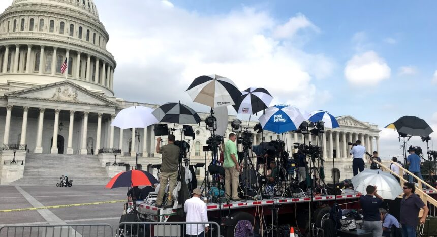 News teams set up before press conference in front of Capitol Hill