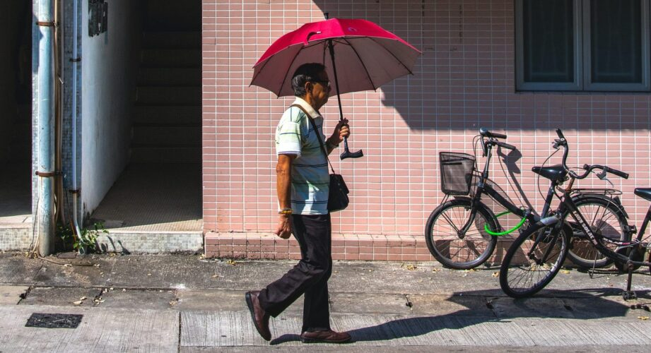 Man on street holding umbrella walking beneath an air conditioner