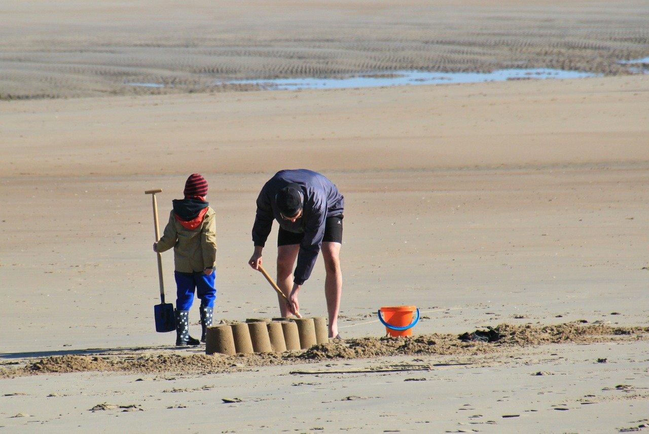 Parent and child make sand castle.
